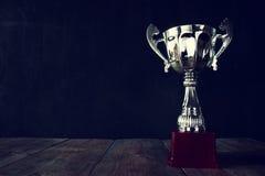 Трофей над деревянным столом и предпосылкой темноты Стоковые Изображения