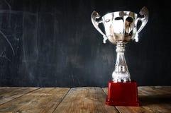 Трофей над деревянным столом и предпосылкой темноты Стоковое Изображение