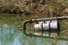 Труба нечистот в озере на плавать barrels стоковое фото