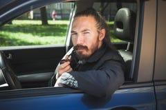 Труба серьезного азиатского человека куря водитель Стоковая Фотография