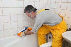Трубка и плитки ванны расчеканки работника Стоковое Фото
