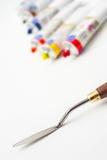 Трубки краски крупного плана и масла ножа палитры на белом холсте Стоковые Изображения RF