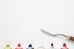 Трубки ножа палитры и краски масла на белом холсте Стоковое фото RF