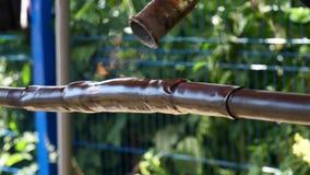 Трубопровод сокращения жары для изоляции проводов перед голубой загородкой на зеленой предпосылке деревьев Рамка Процесс предохра акции видеоматериалы