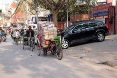 Трудные работая индейцы нажимая тяжелый груз через улицы Дели Стоковая Фотография RF