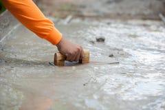 Трудовой штукатуря цемент с лопаткой для пола строения нового для reno Стоковые Фотографии RF