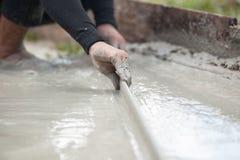 Трудовой штукатуря цемент с лопаткой для пола строения нового для reno Стоковая Фотография RF