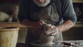 Трудолюбивый старший гончар мочит руки в шаре с водой и касающим опарником глины на закручивая бросать-колесе лучей сток-видео