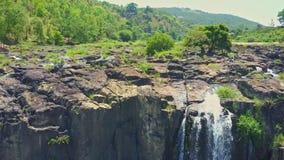 Трутень летает близко над камнями с каскадом водопадов видеоматериал