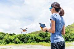 Трутень летания женщины контролируя стоковое фото rf