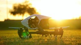 Трутень камеры (UAV) подготавливает для того чтобы лететь на заход солнца