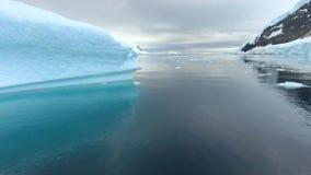 Трутень летает в пролив между голубым айсбергом и берегом Andreev
