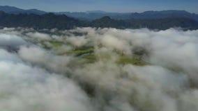 Трутень летает над белыми облаками завихряясь на пиках холма видеоматериал