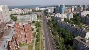 Трутень летает над большим городом с новыми зданиями и дорогами сток-видео