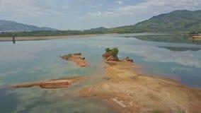 Трутень летает над земельным участком расположенным среди озера против джунглей