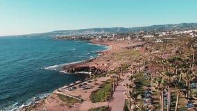 Трутень летает над районом гостиницы с соснами и ладонями Волны моря ударяя скалистый seashore с верхними частями горы на предпос сток-видео