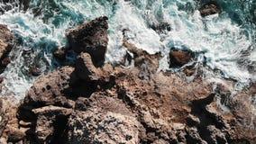 Трутень летает через большие утесы океана Вид с воздуха океанских волн Волны ударяя seashore Волны моря брызгая и создавая пену C сток-видео