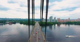 Трутень летания над современным южным мостом вполне управлять автомобилями над красивым рекой Dnieper в Kyiv, Украине солнечно сток-видео