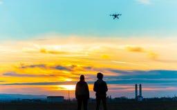 Трутень над деревней на пасмурном заходе солнца с его пилотом стоковые изображения rf