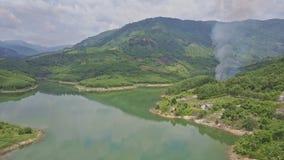 Трутень причаливает зеленым холмам за озером с контролируемым огнем