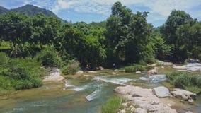 Трутень причаливает парням идя над камнями около реки к джунглям сток-видео