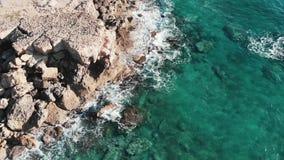 Трутень снятый над ясными прозрачными волнами моря встречая скалистый пляж со скалами брызгая и создавая белую пену Вид с воздуха видеоматериал