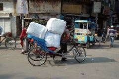 Трудные работая индейцы нажимая тяжелый груз через улицы Дели Стоковая Фотография