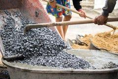 Трудовые смешивая цемент и камешки вместе с лопаткоулавливателем для строения n Стоковая Фотография