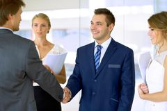 трястить рук бизнесменов 2 уверенно бизнесмена тряся руки и усмехаясь пока стоящ на офисе вместе с Стоковая Фотография