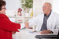 Трясти руки на офисе докторов с его старшим пациентом стоковые фото