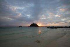 Тряхните тень перед золотыми лучами света рассвета светя через идилличные пляж и океан, предпосылки Стоковое Изображение RF