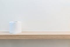 Туалетная бумага свертывает на деревянной полке в ванной комнате стоковая фотография rf