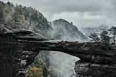 Туманный туманный ландшафт brana Pravcicka строба Pravcicka самый большой естественный свод песчаника в Европе в чехе Швейцарии стоковая фотография