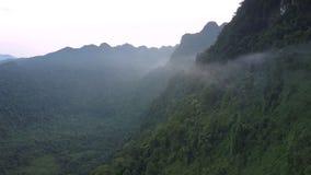 Туманный помох среди высоких крутых горных цепей под серым небом видеоматериал