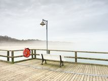 Туманный сумрак на пристани рыбной ловли ориентир ориентира, перила пристани Деревянная моль стоковые фотографии rf