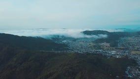 Туман начинает покрывать городок, вид с воздуха 4k видеоматериал