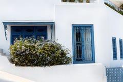 Тунисские восточные дома двора с белыми стенами и голубыми дверями окон Стоковая Фотография
