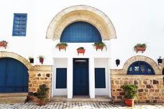 Тунисские восточные дома двора с белыми стенами и голубыми дверями окон Стоковые Фото