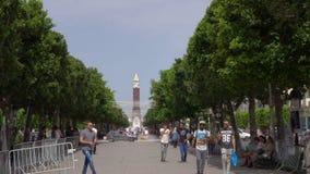Тунис, Тунис - 6-ое июня 2018: Арабские люди идя на бульвар Bourguiba на предпосылке большого Бен башни с часами известно акции видеоматериалы