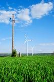 Турбины энергии ветра и старая передача возвышаются на поле стоковое фото rf