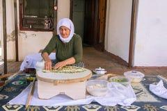 Турецкая женщина делает традиционное национальное блюдо - испеченный плоский блинчик Gozleme стоковая фотография