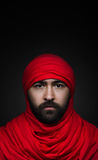 Турецкая и арабская тема: красивый мусульманский человек с бородой в красном головном платке изолированном на черной предпосылке  Стоковые Фотографии RF