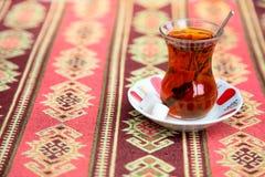 Турецкий чай в традиционной стеклянной чашке на handmade арабском tableclo стоковое фото rf