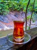 Турецкий чай на деревянном столе взгляды реки на заднем плане стоковая фотография rf