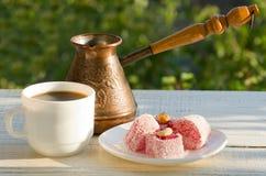 Турецкое наслаждение, кружка кофе и Cezve в солнечном свете на предпосылке зеленого, приятного вечера Стоковое Изображение RF