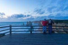 2 туриста в 12 апостолах в большой дороге океана в Австралии Стоковое Фото