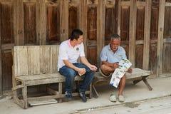 Туристические гиды сидят на входе до одно из общежитий в Chiang Khan, Таиланде Стоковые Фотографии RF