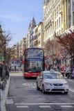 Туристический автобус и такси обеспечивают циркуляцию на улице в Мадриде Стоковые Фотографии RF