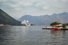 Туристическое судно в заливе между горами, шлюпке такси на пристани на переднем плане стоковое изображение