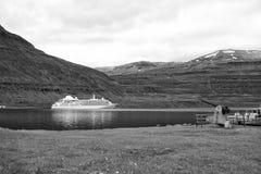 Туристическое судно в фьорде Sejdisfjordur, Исландии Океанский лайнер в гавани моря на ландшафте горы Курсировать для удовольстви стоковые изображения
